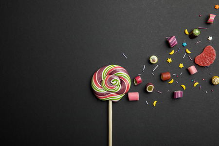 Top view of delicious multicolored round lollipop on wooden stick with candies and sprinkles on black background