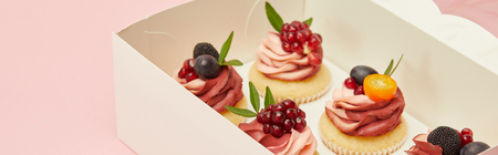 Panoramic shot of cupcakes with berries and fruits in cardboard box isolated on pink background