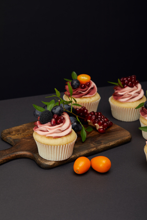 sweet cupcakes with fruits and berries and cutting board on grey surface isolated on black Banco de Imagens