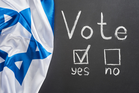Top view of vote lettering and check mark in square near yes word on black chalkboard near flag of Israel