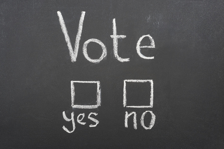 Top view of white vote, yes and no words on black chalkboard Imagens