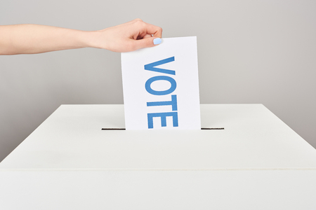 Cropped view of woman putting card with vote in box isolated on grey background 스톡 콘텐츠