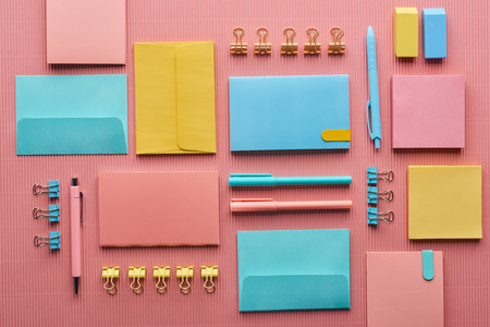 Flat lay of colorful stationery supplies on pink background