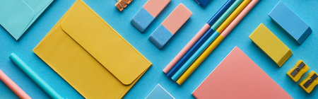 Panoramic shot of envelope and arranged colorful stationery isolated on blue background