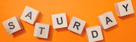 Panoramic shot of wooden cubes with letters on orange surface 写真素材