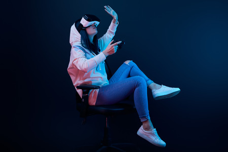 Brunette woman holding joystick and gesturing while wearing virtual reality headset on blue background 免版税图像