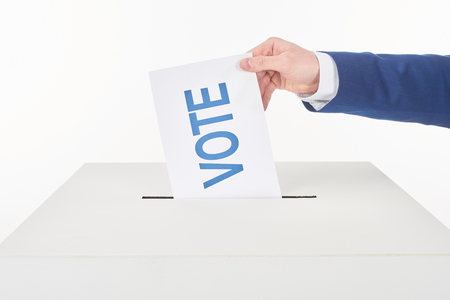 Partial view of man putting card with vote lettering in box isolated on white background