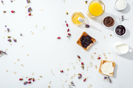 Top view of toasts with jam and cream cheese near honey, glass of orange juice and jug with milk on white background Banque d'images - 122292952