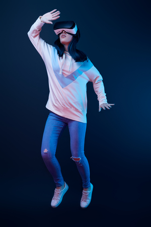 Young woman gesturing while using virtual reality headset and jumping on blue background 免版税图像