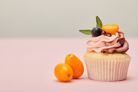 Cupcake with ripe kumquats on pink surface isolated on grey background