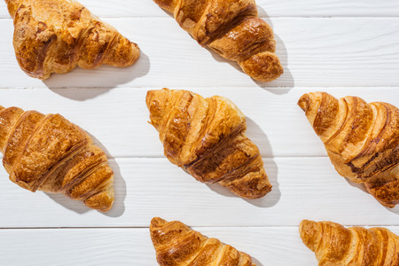 Flat lay of delicious and sweet croissants on white surface