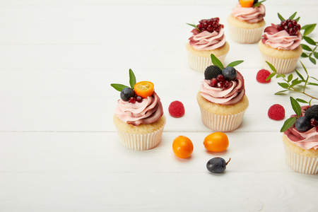 cupcakes with berries and cream on white surface