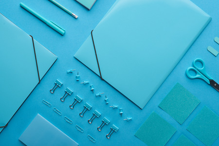 Flat lay of paper binders and organized stationery isolated on blue background