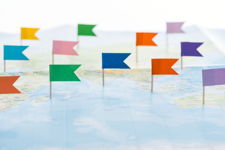 Selective focus of colorful stationery flag pins on world map