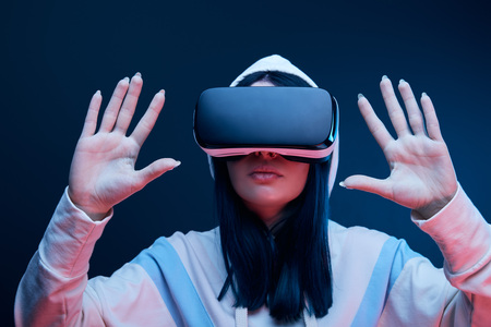 selective focus of brunette girl in hood gesturing while virtual reality headset on blue