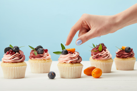 partial view of woman with sweet cupcakes with berries Banco de Imagens