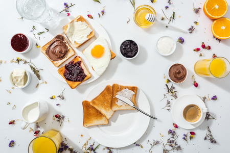 Top view of plates with tasty toasts near drinks and oranges on white background
