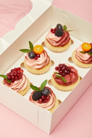 sweet cupcakes with fruits and berries in box isolated on pink