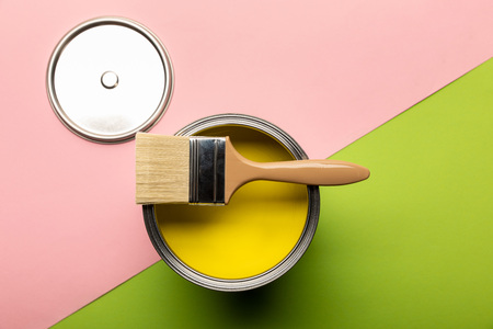 Top view of tin with yellow paint and brush on pink and green surface Standard-Bild - 122293119