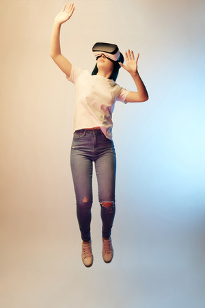 Young woman in virtual reality headset gesturing while levitating on beige and blue background Stock Photo - 122293122