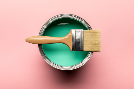 Top view of tin of green paint and brush on pink surface Standard-Bild - 122293164