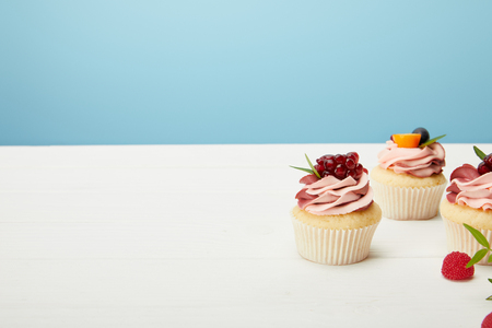 Cupcakes with berries and cream on white surface isolated on blue background