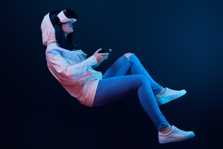 Brunette woman levitating and holding joystick while playing video game and wearing virtual reality headset on blue background Stock Photo - 122293177