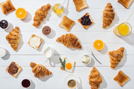 Top view of sweet croissants near tasty toasts and drinks on white background Reklamní fotografie