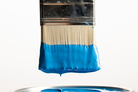 Close up view of brush with blue paint over can isolated on white background Standard-Bild - 122293190