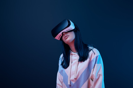 young brunette woman wearing virtual reality headset on blue 写真素材
