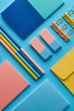 Top view of notebooks and colorful stationery isolated on blue background