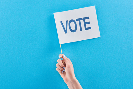 Cropped view of woman holding flag with vote lettering on blue background with copy space