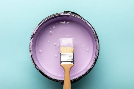 Vue de dessus du seau avec peinture violette et pinceau sur fond bleu Banque d'images
