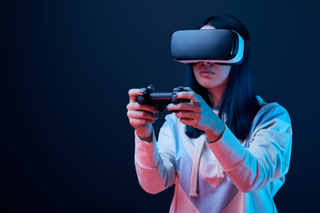 Selective focus of brunette woman playing video game while wearing virtual reality headset on blue background