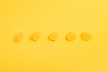 Top view of delicious sugary jellies in row on yellow background