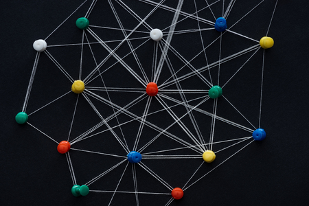 Top view of push pins connected with strings isolated on black, network concept Stockfoto