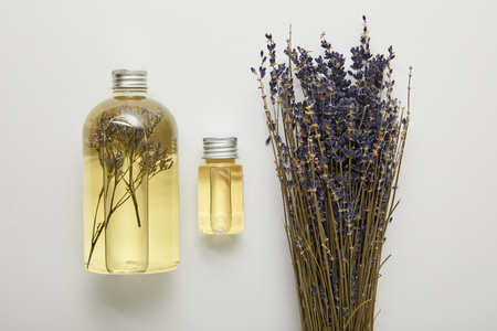 Top view of transparent bottles with natural liquid yellow beauty products near dry purple wildflowers on grey background