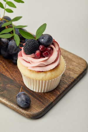 Cupcake with cream and grapes on cutting board isolated on grey background Stock Photo