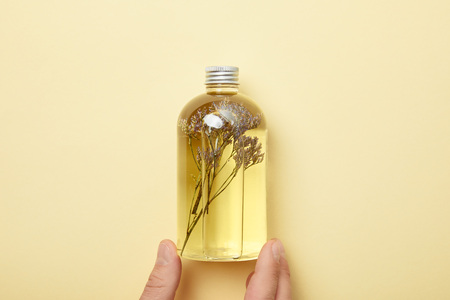 Cropped view of man holding bottle with natural beauty product and herbs on yellow background
