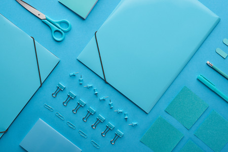 Flat lay of paper binders, paper clips and various stationery isolated on blue background