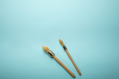 Top view of two brushes on blue surface
