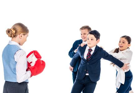 Alumna en guantes de boxeo con escolares intimidación colegial aislado en blanco Foto de archivo