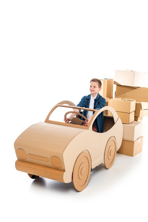 happy boy playing with cardboard car on white with copy space Фото со стока