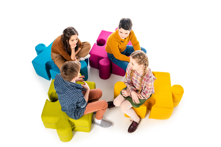 High Angle View of kids sitting on jigsaw puzzle poufs and talking Isolated On White