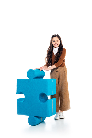 smiling kid with jigsaw puzzle piece looking at camera on white Stock Photo