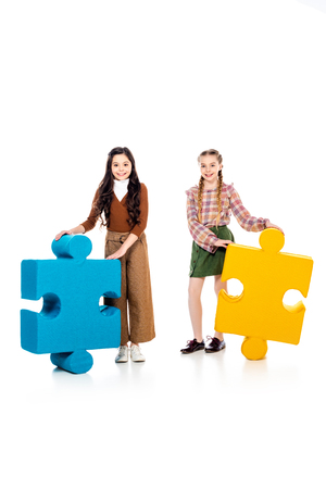 smiling kids with jigsaw puzzle pieces looking at camera on white Stock Photo