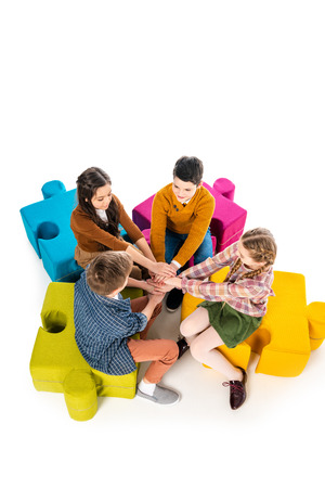 High Angle View of kids sitting on jigsaw puzzle poufs and Stacking Hands Isolated On White