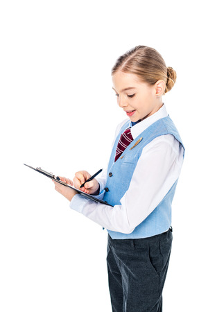 adorable schoolgirl in formal wear writing in clipboard with pen Isolated On White