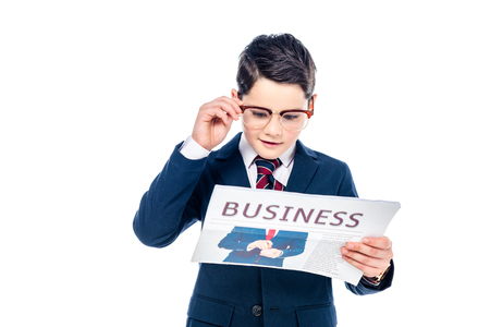 schoolboy in formal wear and glasses reading business newspaper Isolated On White Stockfoto