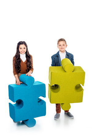 happy kids with jigsaw puzzle pieces looking at camera on white